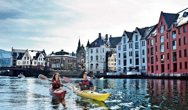 Two people kayaking in the fjord city Ålesund, Norway