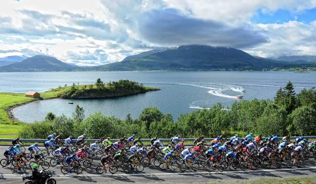 The peloton of the Arctic Race of Norway cycling in the scenic landscape of Northern Norway