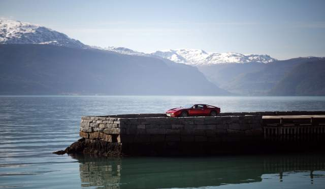 A car on a pier of a lake with the beautiful, snow-capped mountain tops in the background
