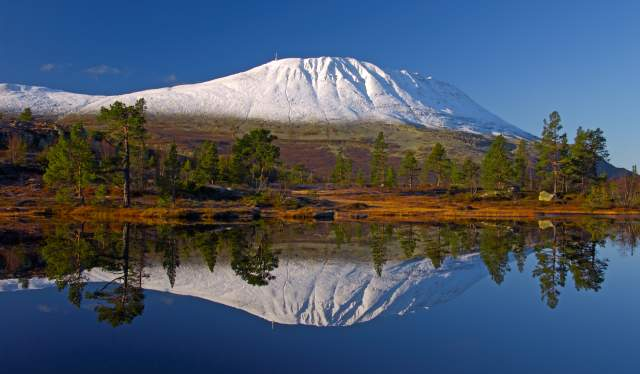 A snowclad Mount Gaustatoppen reflected in a lake