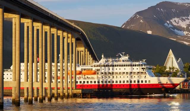 Hurtigruten sailing under a bridge in Tromsø
