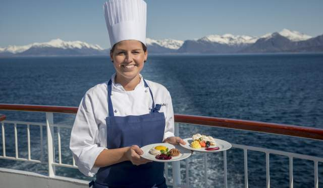 A woman chef standing on the deck of Hurtigruten with two plates of food