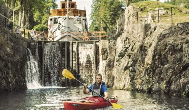 Un hombre rema a bordo de un kayak a través del canal de Telemark, en el Este de Noruega.