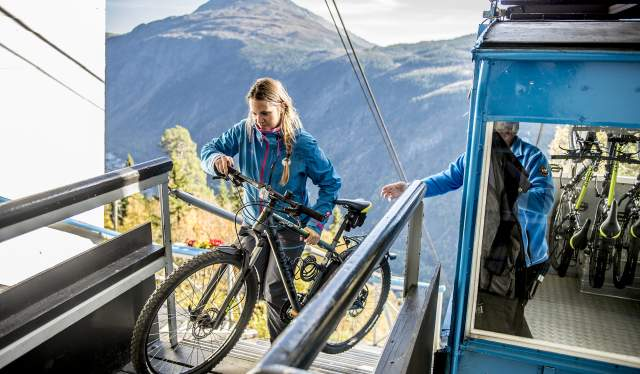 A person lifting a bike out of the Krossobanen cable car. Telemark, Norway