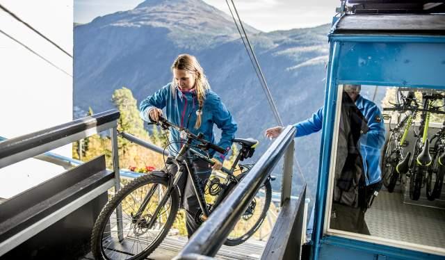 En person løfter en cykel ud af en gondol på Krossobanen i Telemark, Norge
