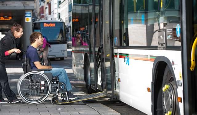 En mann i rullestol får hjelp til å komme seg inn på en buss