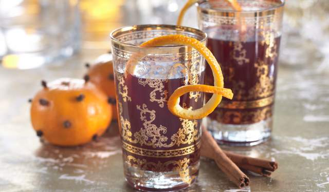 Two glasses of gløgg with cinnamon sticks and mandarins pierced with cloves