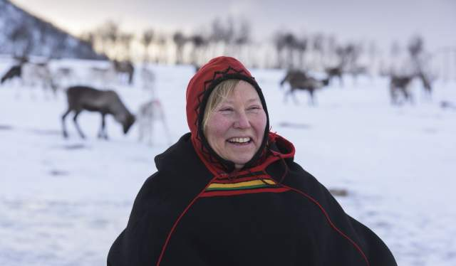 A woman in a traditional Sami costume, with snow and reindeer in the background, Northern Norway