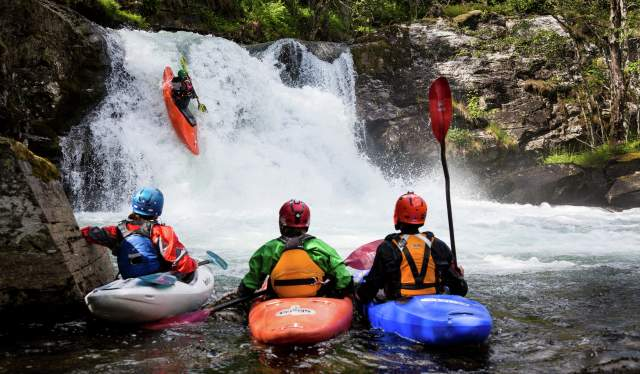 Four people whitewater kayaking at the Ekstremsportsveko in Voss, Fjord Norway
