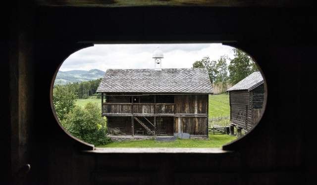 View on a wooden shed through a hole in the wooden wall at Sygard Grytting, Eastern Norway
