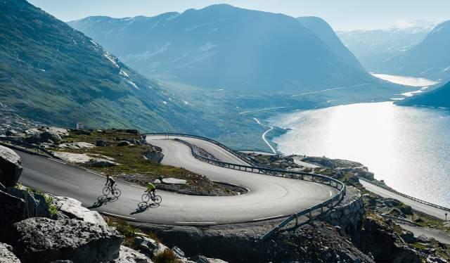 To personer sykler opp en svingete vei ved Geirangerfjorden