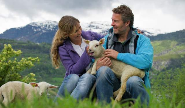 A couple cuddling a lamb in the mountains in Fjord Norway