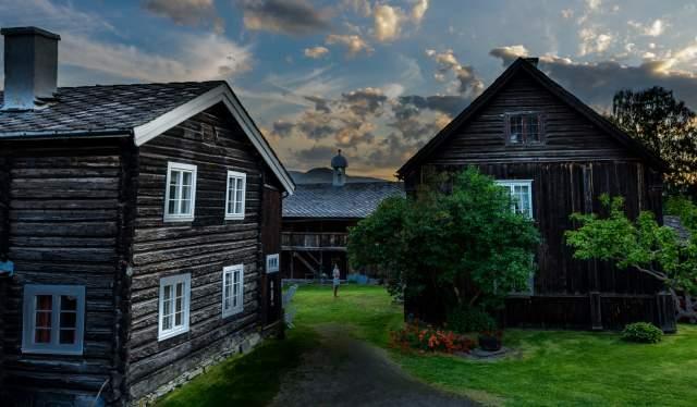 Gamle trehus i sommerlandskap på Sygard Grytting historiske hotell