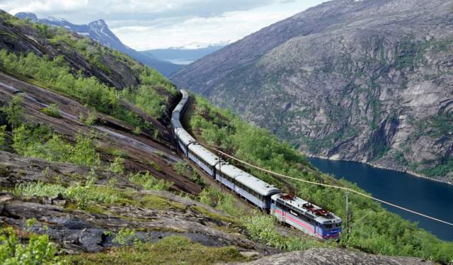 A train on the Ofotbanen in a beautiful river and mountain landscape, Northern Norway