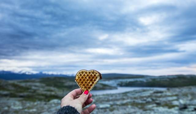 A hand holding op a heart-shaped waffle with beautiful scenery in the background