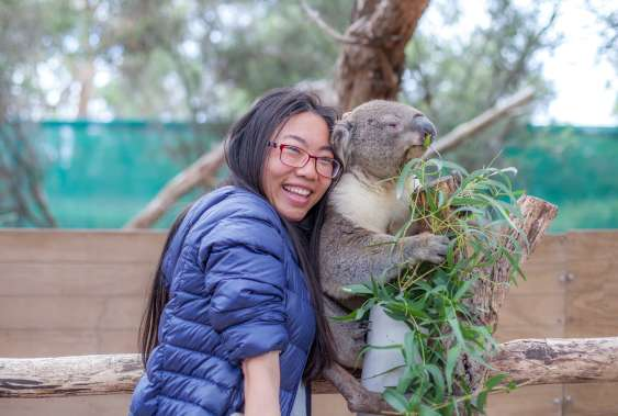 Female tourist taking selfie with a koala at Moonlit Sanctuary Wildlife Conservation Park