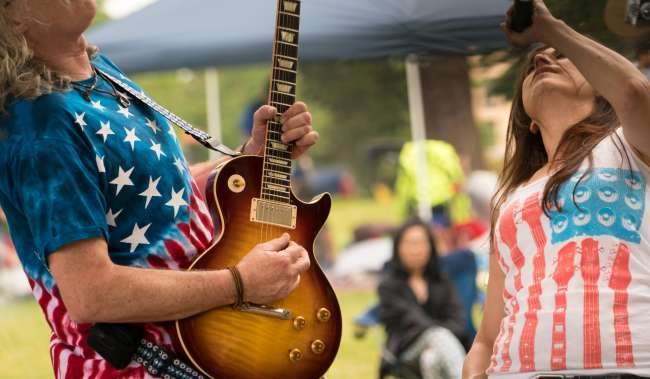 Guitar Player in American Flag shirt playing concert at 4th of July at Angle Lake Park
