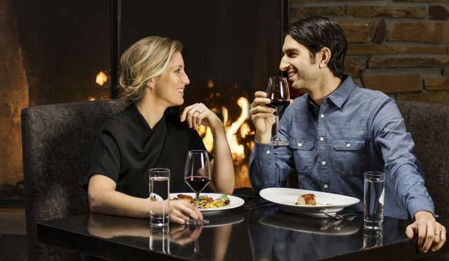 Couple eating a meal by the fireplace at Copperleaf Restaurant