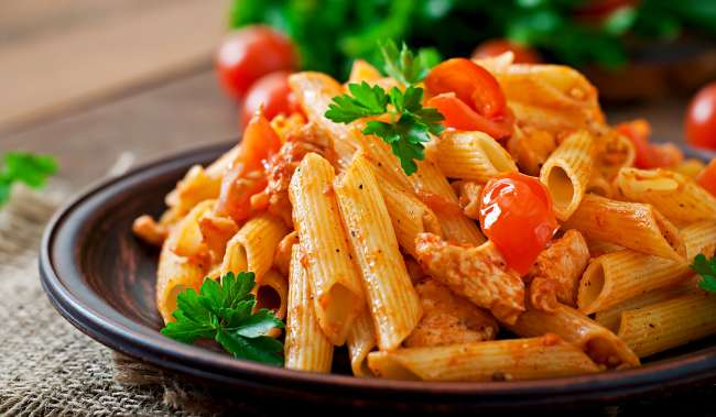 Penne pasta in tomato sauce with chicken, tomatoes decorated with parsley on a wooden table