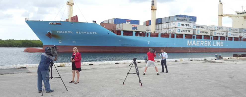 Photo of two reporters and videographers reporting from dockside with large cargo ship in the background.
