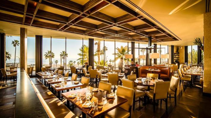 A Glass Paned Raw Bar Surrounded By Bank Of Chairs Wood Fire Oven Architecture That Offers Second Floor Views The Pier While Also Bringing To