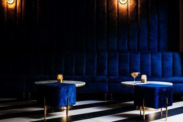 Plush navy blue velvet banquettes with a martini on a cocktail tables