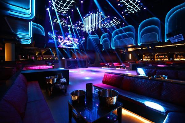 Dark nightclub with purple and blue lights shining all around the room.