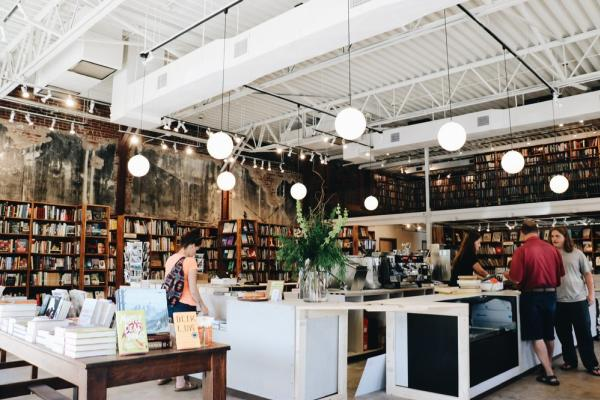 An interior photo of The Dusty Bookshelf store in Manhattan, wooden shelbes on the walls filled with books and customers browsing the selection