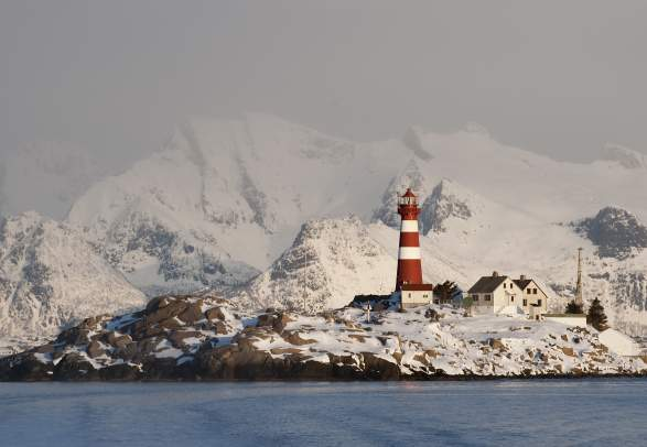 View on the Skrova lighthouse and the snowy mountains, Skrova, Northern Norway from the sea