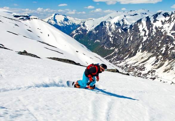 En person står på snowboard ned fjellsiden i Stryn