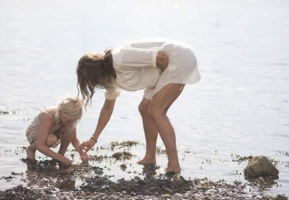 Mor og barn leker på stranden i Moss