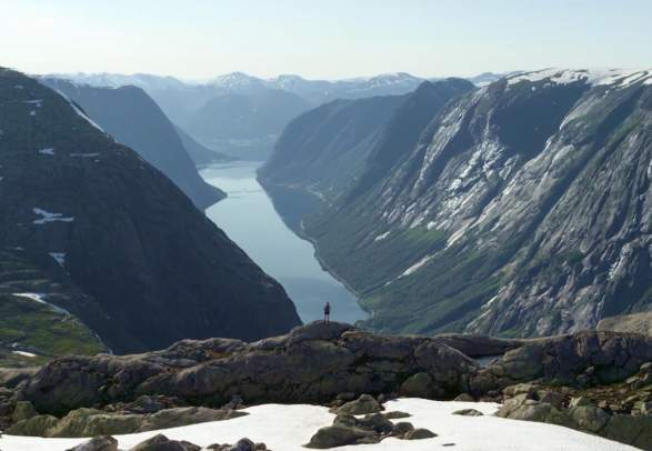 A man standing on a mountain with a view of Fjord Norway