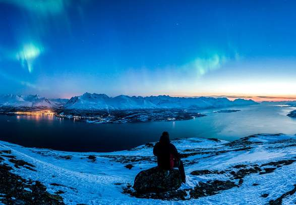 Person watching the northern lights over the Lyngen alps