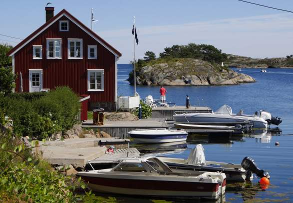 View of a house near the water and a few boats in Sandøya outside of Tvedestrand, Southern Norway