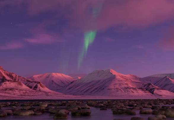Northern lights and pink sky over snow-covered mountains in Svalbard