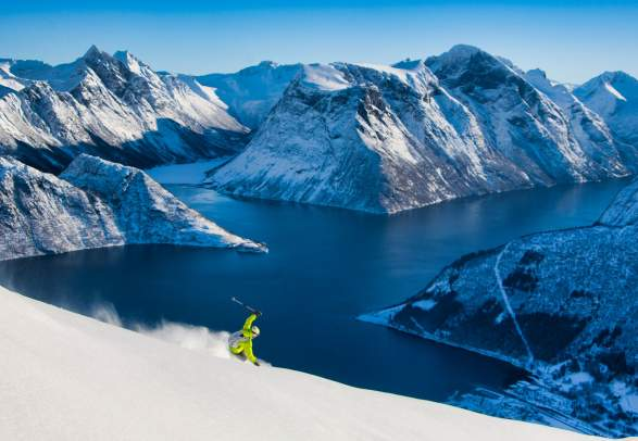 A ski tourer on their way down the mountain towards the Hjørundfjord in Fjord Norway