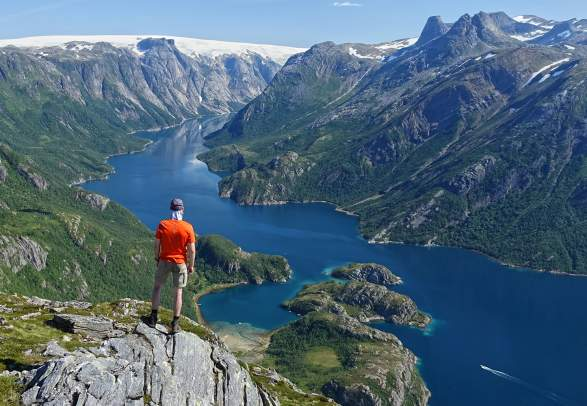 Person on mountain top looking down on Nordfjorden in Rødøy, Helgeland