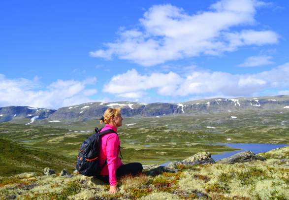 A woman sitting and enjoying the view of the mountains in Ål in Hallingdal, Eastern Norway
