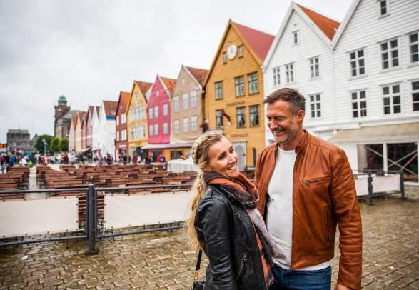 Et muntert par smiler fra bryggen i Bergen på Vestlandet