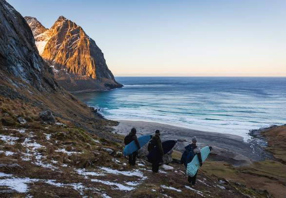Three surfers with surf boards under their arms looking down at a bay in winter, Lofoten islands, Norhern Norway