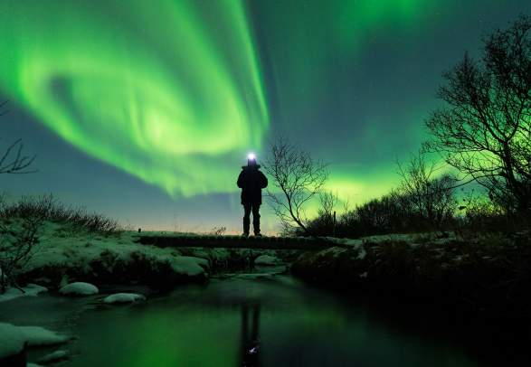 A person standing close to a lake in Varanger surrounded by northern lights