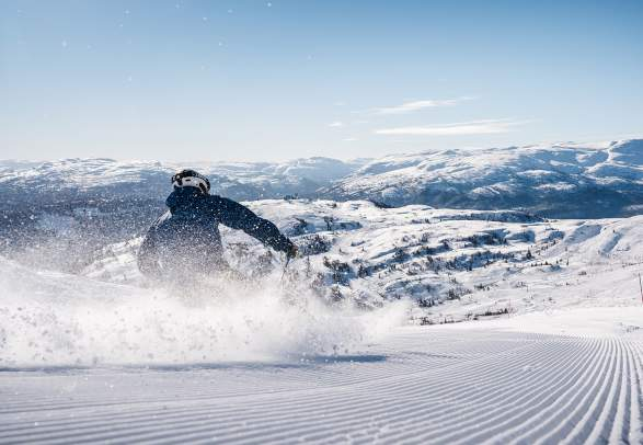A person is downhill skiing at Voss Resort in Fjord Norway on a sunny day