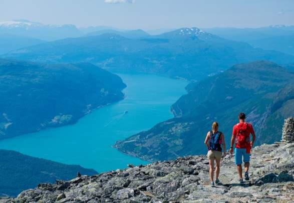 Et par går på tur i fjellet med utsikt over Nordfjord