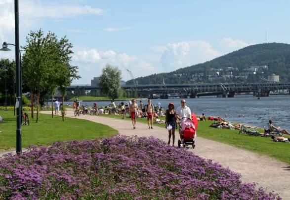 Mennesker som går langs Drammenselva om sommeren