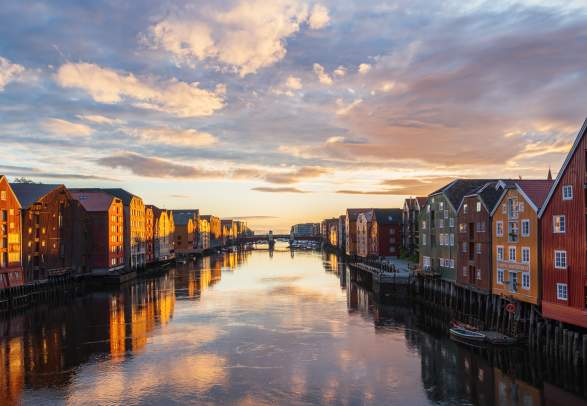 Sunset over the old wooden houses along the Nidelven river in Trondheim in Trøndelag, Norway