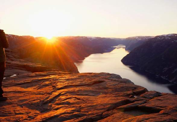 A person watching the sunrise at Preikestolen (The Pulpit Rock) in Ryfylke in Fjord Norway