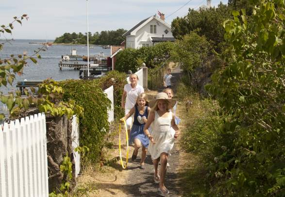 A group of children running along a white picket fence on Merdø island in Arendal, Southern Norway.