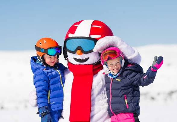 Two kids are hugging Valle the snowman at the slopes in Trysil, Eastern Norway