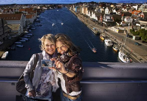 Two women taking a selfie with Haugesund city in the background