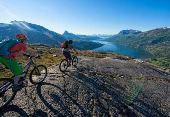 Two people biking down the Narvikfjellet mountain in Narvik, Northern Norway